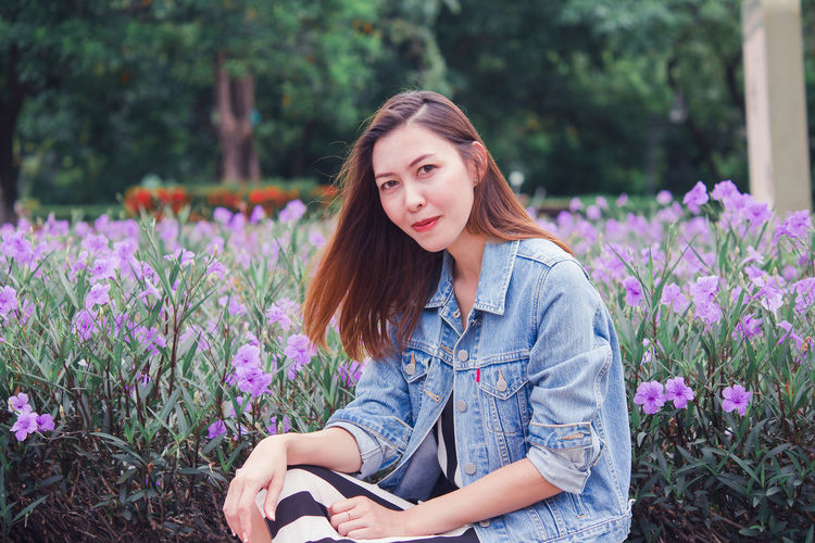 Beautiful young woman sitting on purple flowering plants
