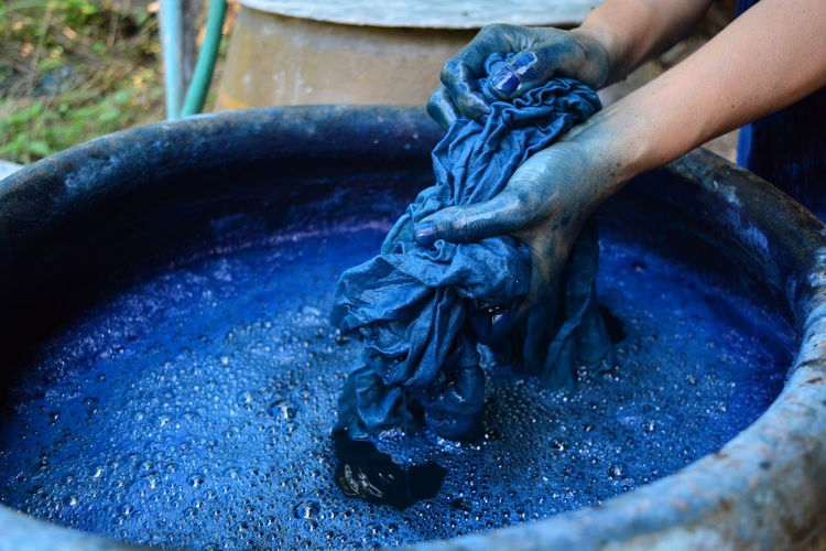 Cropped hands of woman washing textile in blue water