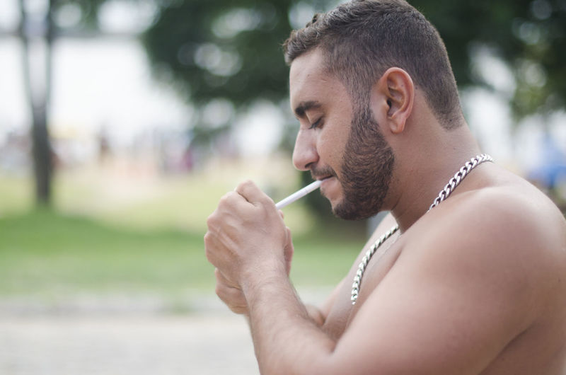 One Person Focus On Foreground Headshot Young Adult Holding Side View Portrait Leisure Activity Cigarette  Lifestyles Real People Smoking Issues Smoking - Activity Social Issues Bad Habit Adult Day Outdoors Profile View