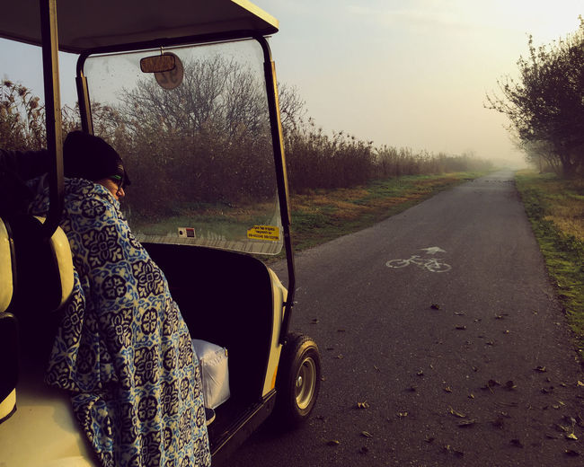 Boy Sitting In Golf Cart On Road