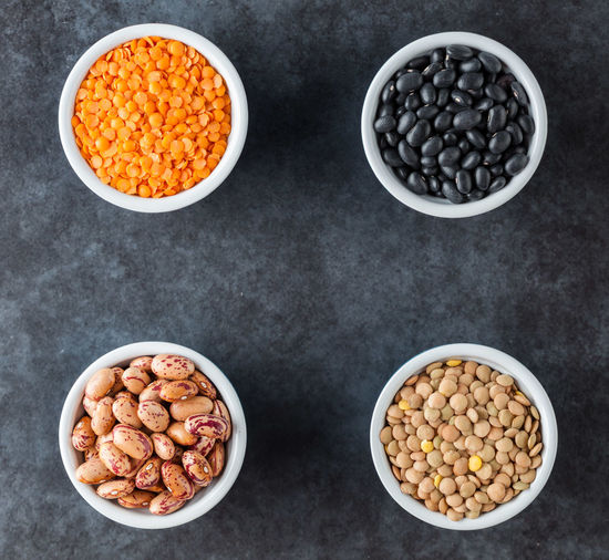 Red and brown lentils, heirloom beans, and black turtle beans on dark grungy surface. Top view with copy space. Copy Space Bean Bowl Brown Close-up Day Food Food And Drink Freshness Healthy Eating Heirloom Indoors  Legume Family Lentils No People Raw Food Still Life Top View Turtle Beans Variation Vegetable Vegetarian Food