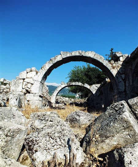 Tlos Antik Kenti, Fethiye- Türkiye Low Angle View Sunlight Built Structure Old Ruin Day Arch Architecture Rock - Object History Outdoors Clear Sky Ancient Mountain No People Ancient Civilization Blue Sky Nature