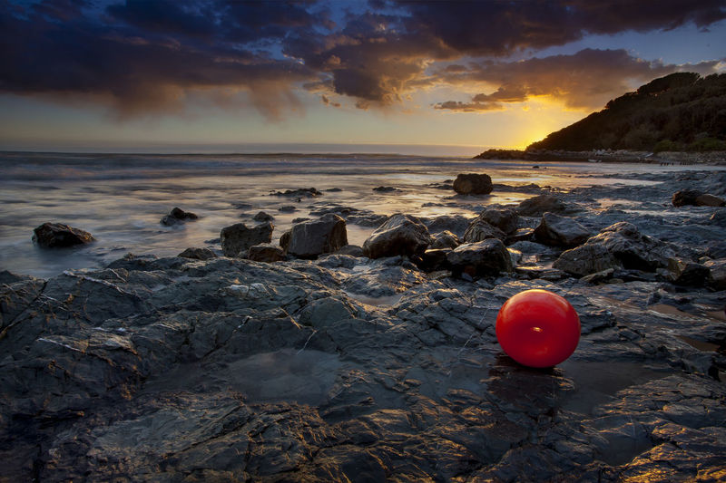 Red Buoy On Rocky Shore Against Sky During Sunset