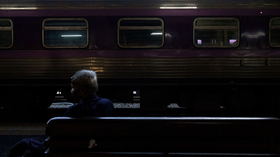 Rear view of man sitting at train