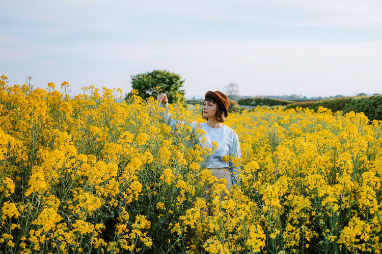 Woman standing amidst flowers against sky