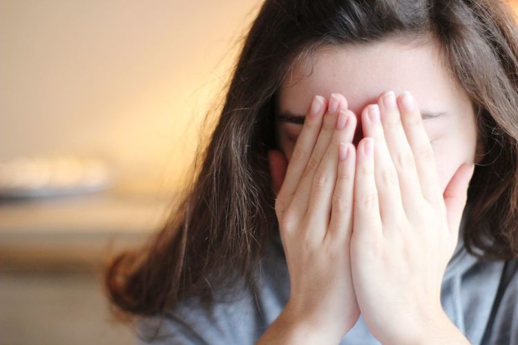 Close-up of woman covering face at home