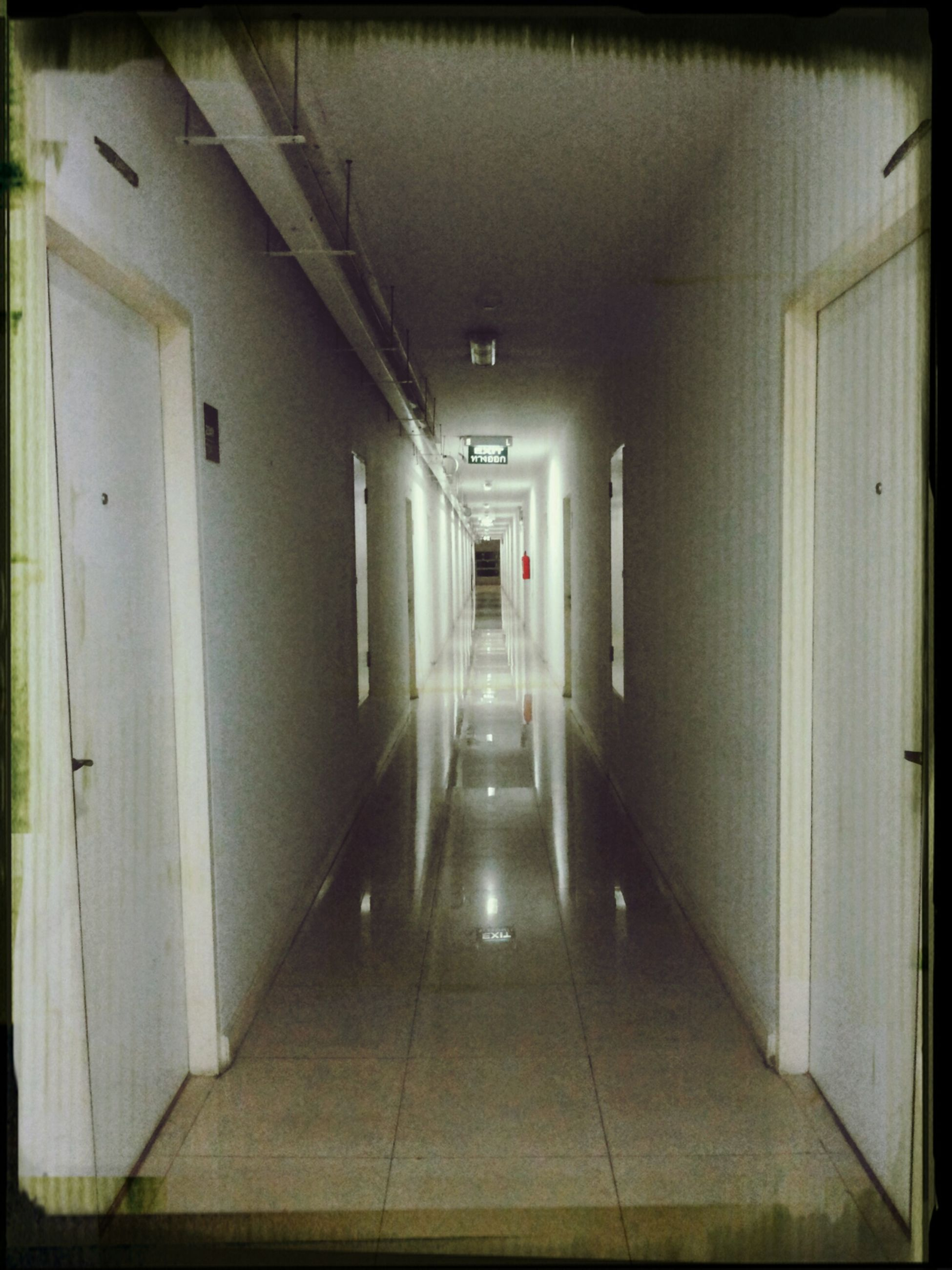 indoors, corridor, architecture, the way forward, built structure, empty, tiled floor, flooring, narrow, door, absence, transfer print, ceiling, diminishing perspective, wall - building feature, wall, auto post production filter, building, no people, illuminated