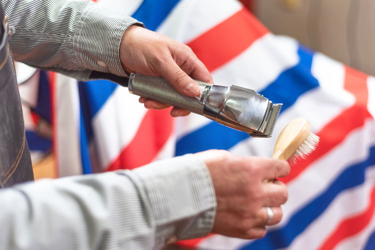 Cropped hands of barber cleaning electric razor in shop