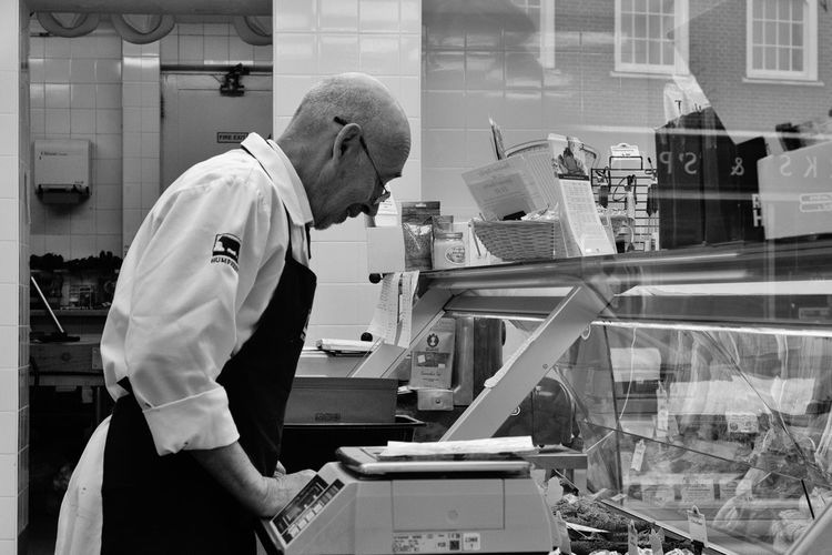 Butchers shop - man at work Butcher Butchery Butcher Shop Occupation One Person Business Adult Real People Working Window Reflection Man At Work Streetphotography Street Photography Streetphoto_bw Black And White Black And White Photography EyeEm Best Shots Butchers Counter Working Man Standing Shop Counter Shop Apron Clothing Mature Adult Profile View