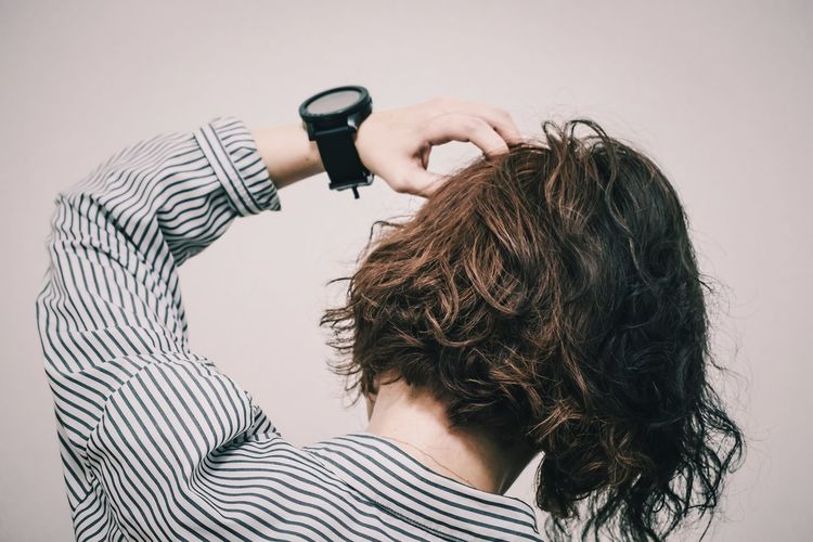 Rear view of woman with hand in hair against white background