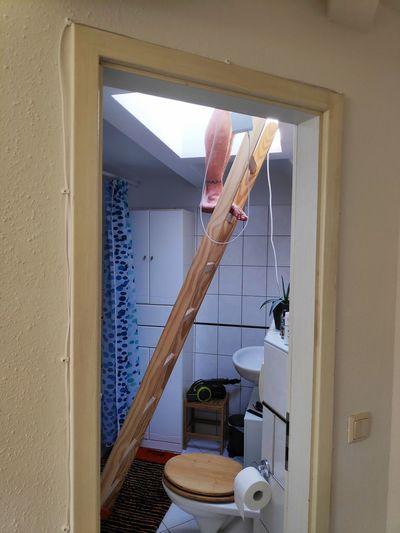Man climbing a ladder in his bathroom