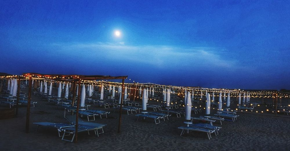 Panoramic shot of chairs on beach against sky at night