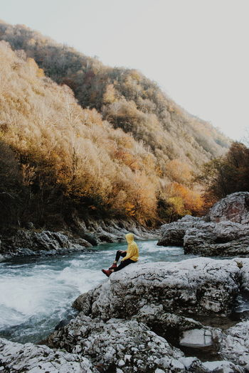 Person sitting on rock by stream in forest