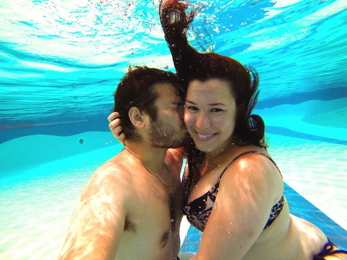 Shirtless Man Kissing Happy Beautiful Woman In Swimming Pool