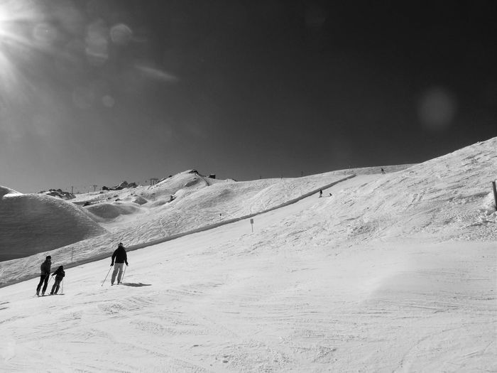 People Skiing On Snow Covered Mountain Against Sky