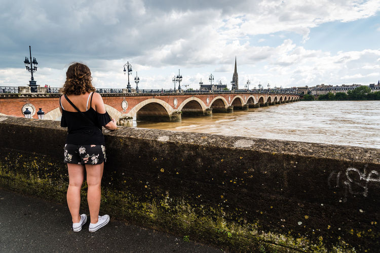 Woman standing on promenade by river against sky