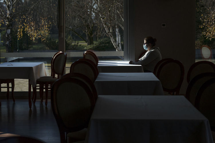 Woman sitting on chair in restaurant