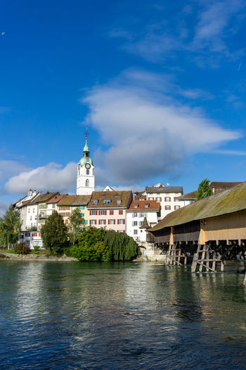 River amidst buildings against blue sky