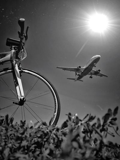 Low Angle View Of Bicycle With Airplane Flying Against Sky On Sunny Day