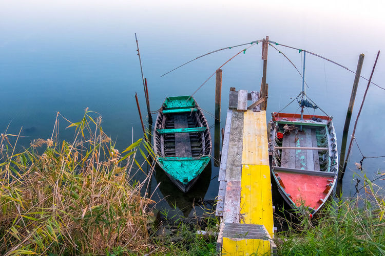 Fishing boats moored in lake against sky