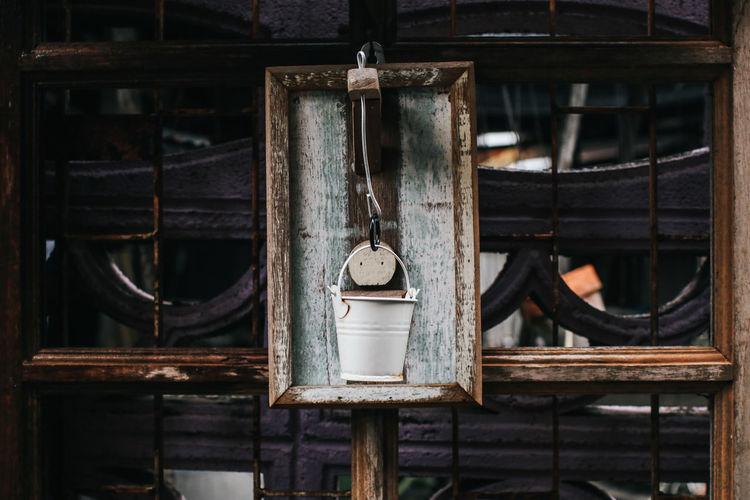 Old rusty bucket hanging outdoors