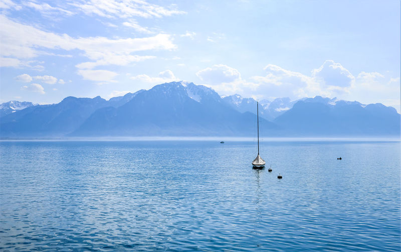 Sailboats in sea against mountains in montreux. switzerland.