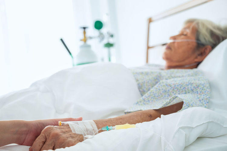 Senior Woman Lying On Bed With Iv Drip On Hand In Hospital