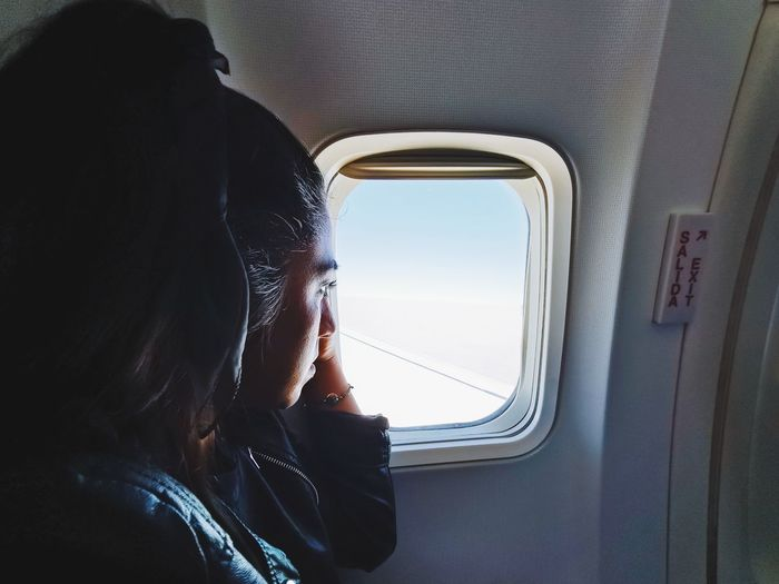 Woman looking through window in airplane