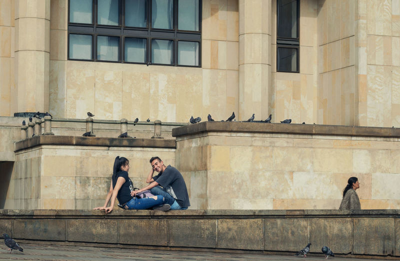 Full length of couple sitting in city