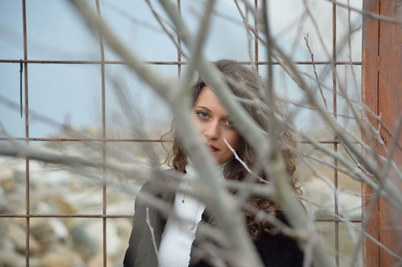 Portrait of young woman against fence