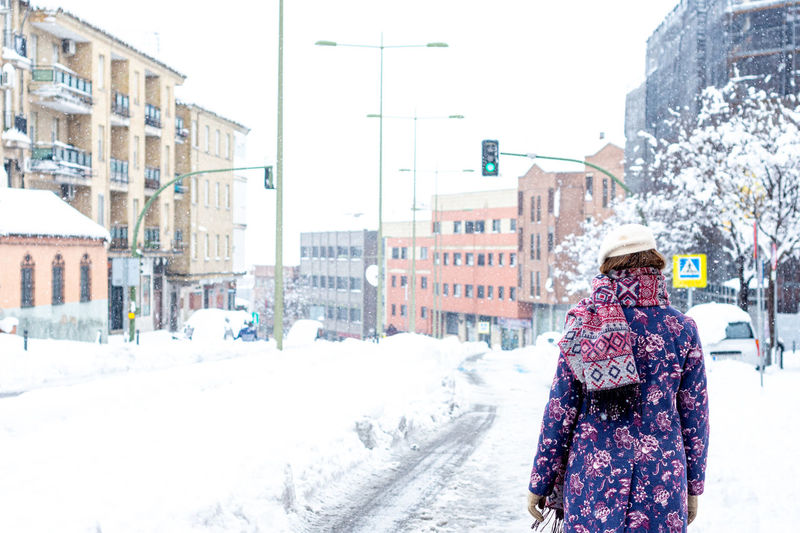 Man in snow on city street during winter