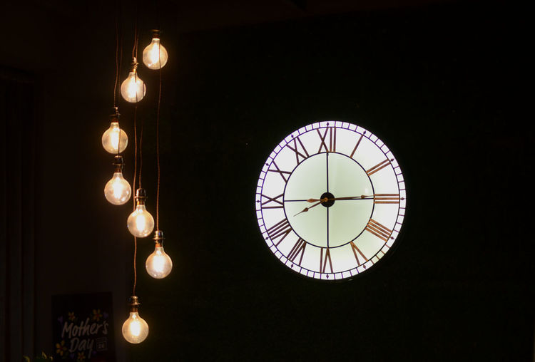 Clock Illuminated Time Low Angle View Lighting Equipment Hanging No People Indoors  Roman Numeral Clock Face Circle Architecture Pendant Light Night Instrument Of Time Minute Hand Light Geometric Shape Light Bulb Electricity  Ceiling Light Fixture Lightbulb