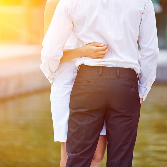 Midsection of couple embracing on field during sunny day