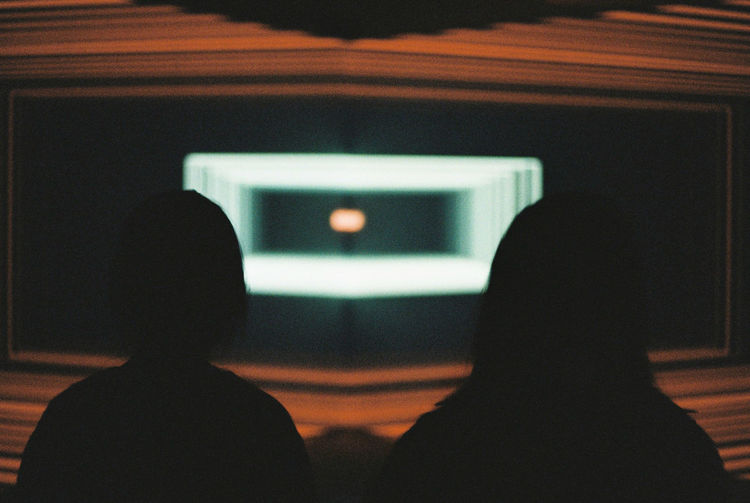 Rear view of silhouette people sitting in illuminated stage