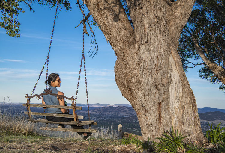 Man sitting on swing at playground against sky