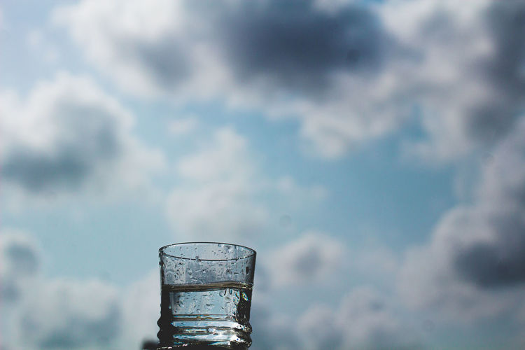 Glass of water against cloudy sky