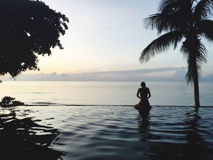 Rear view of woman relaxing at infinity pool against sea