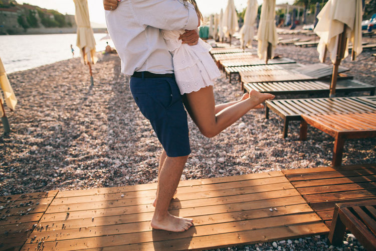 Low Section Of Man Lifting Woman While Standing On Wood At Beach