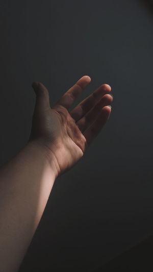 Close-up of person hand against gray background