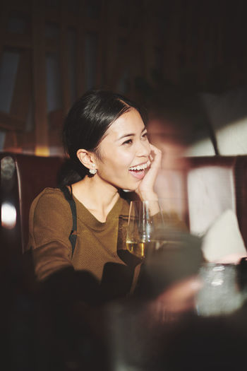 Laughing woman looking away while sitting at restaurant
