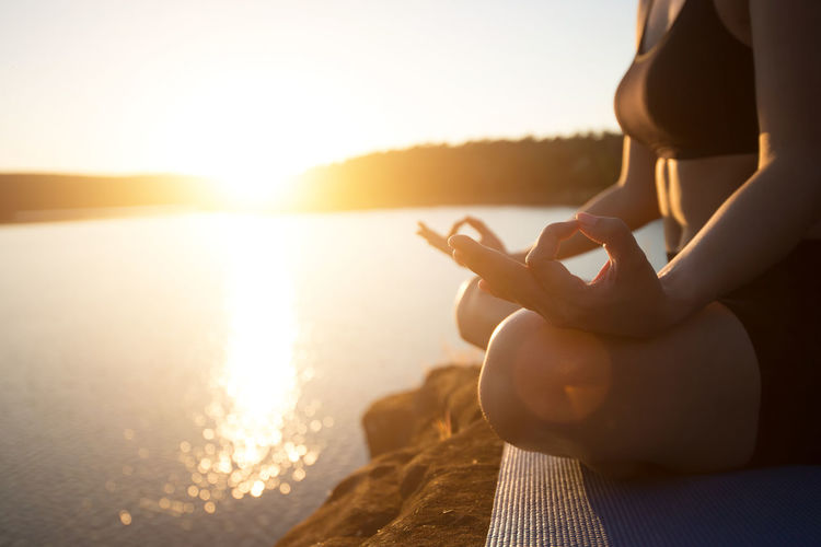Midsection of woman meditating while sitting on rock at lakeshore during sunset