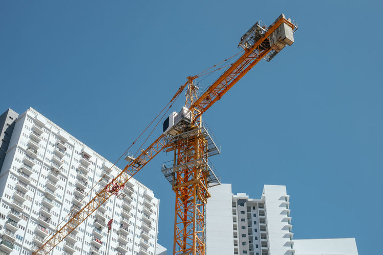 Low angle view of tower crane by building against clear sky