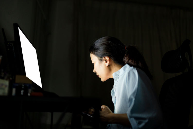Side view of a woman working on computer