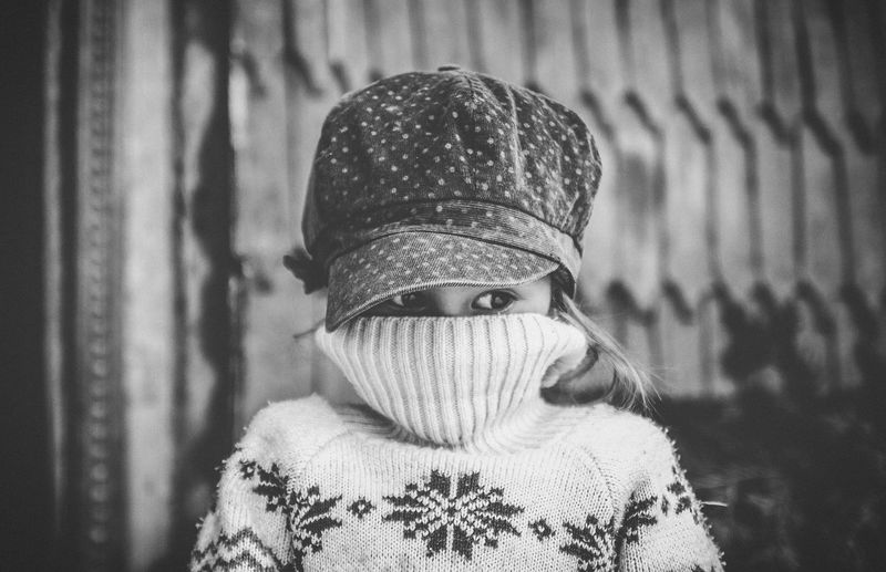 Innocence moments Shy and beautiful childhood eyes are the proof of pure innocence. Portrait Headshot Sweater Hat One Person Clothing Focus On Foreground Real People Close-up Front View Warm Clothing Looking At Camera Knit Hat Young Adult Leisure Activity Obscured Face Hairstyle Scarf Day Lifestyles