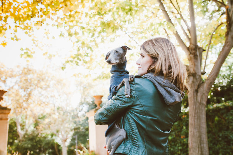 Rear view of woman holding dog standing outdoors