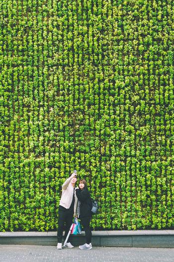 Streets Of Myeongdong 2016: Green Wall Selfie Seoul South Korea MyeongDong Travel Couple Selfie Green Greenery Plants Wall Romance Romantic The Street Photographer - 2016 EyeEm Awards Street Photography