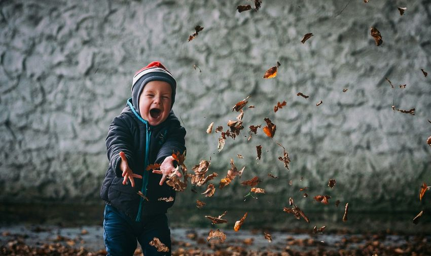Preschool boy in warm clothing throwing autumn leaves in mid-air