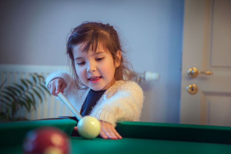 Cute girl playing pool at home