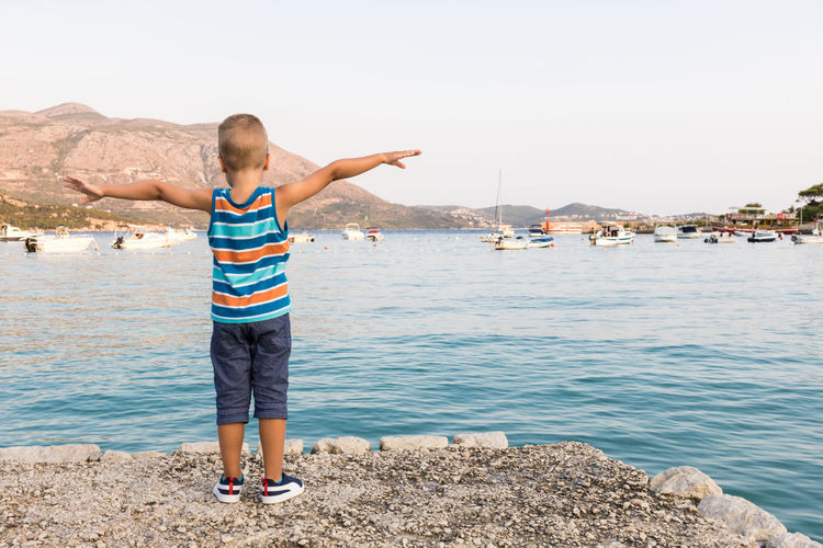 Rear view of boy standing on rock by sea against sky