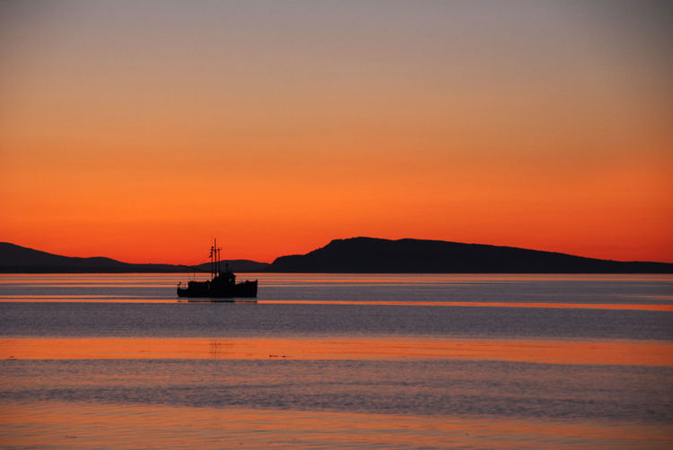 Silhouette boat sailing on sea against orange sky
